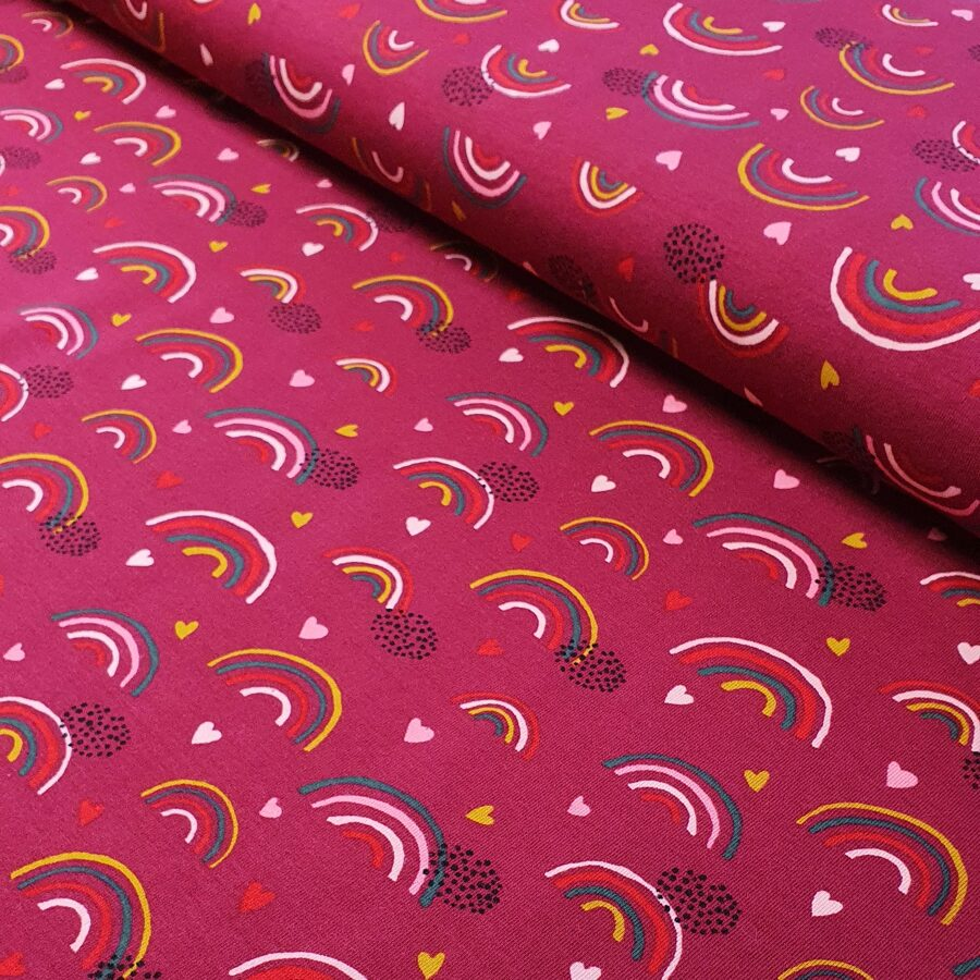 Varavīksne un sirsniņas uz aveņu rozā fona plānā kokvilnas trikotāža